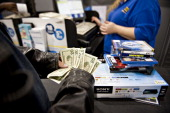 A customer counts his money as he prepares to pay for merchandise at a Best Buy Co store ahead of Black Friday in Peoria Illinois US on Thursday Nov...