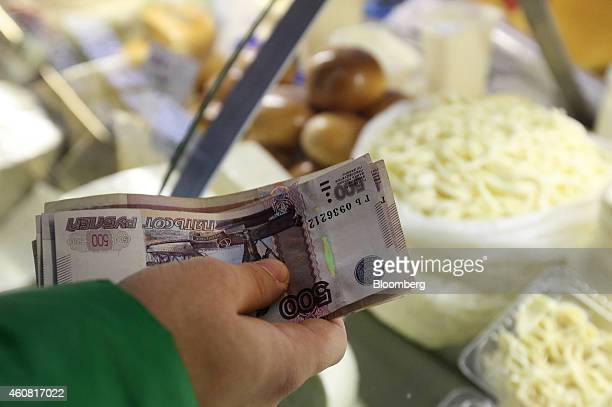 A customer counts out ruble banknotes at a stall selling dairy products inside the Dorogomilovsky food market in Moscow Russia on Tuesday Dec 23 2014...