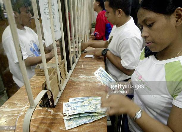 A customer counts peso bills at a currency trading shop in the financial district of Makati suburban Manila 24 August 2003 The Philippine currency...