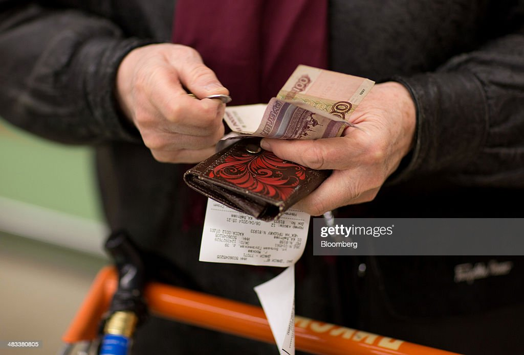 A customer counts ruble notes and coins to pay for goods inside a Dixy supermarket operated by OAO Dixy Group in Moscow, Russia, on Tuesday, April 8, 2014. Suppliers suffering from ruble depreciation this quarter are urging retailers to increase prices. Photographer: Andrey Rudakov/Bloomberg via Getty Images