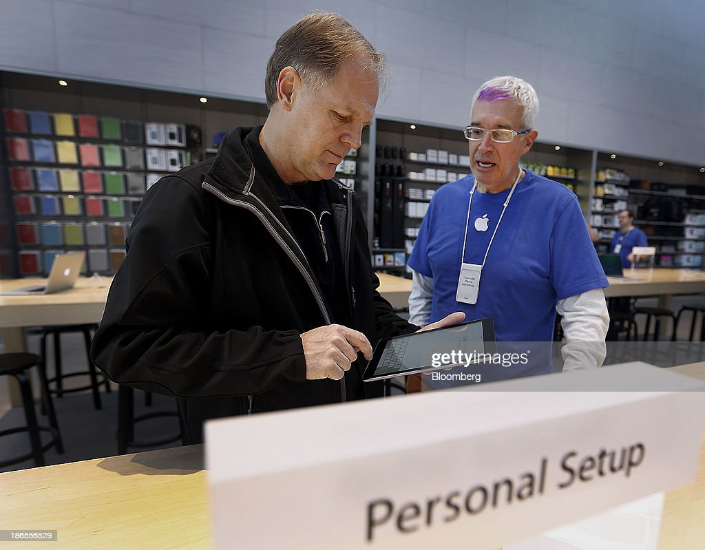 Customer <a gi-track='captionPersonalityLinkClicked' href=/galleries/search?phrase=Dale+Scott&family=editorial&specificpeople=243427 ng-click='$event.stopPropagation()'>Dale Scott</a>, left, gets help from an employee with setting up a new Apple Inc. iPad Air at a store in Palo Alto, California, U.S., on Friday, Nov. 1, 2013. Apple Inc.'s forecast for the slowest holiday sales growth in a half decade reflects how iPhones and iPads aren't providing the growth surges they once did as competition accelerates in the saturated mobile market. Photographer: Tony Avelar/Bloomberg via Getty Images