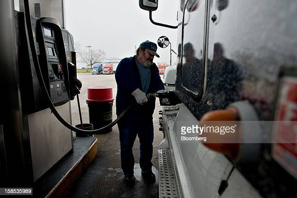 Customer Dave Graves fills his truck with fuel at a gas station in Princeton Illinois US on Tuesday Dec 18 2012 Retail gasoline in the US fell to the...