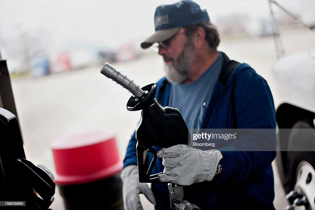 Customer Dave Graves returns the pump after filling his truck with fuel at a gas station in Princeton, Illinois, U.S., on Tuesday, Dec. 18, 2012. Retail gasoline in the U.S. fell to the lowest level in a year as refineries restored production and stockpiles rose to an eight-month high, blunting criticism of President Barack Obama's energy policies. Photographer: Daniel Acker/Bloomberg via Getty Images