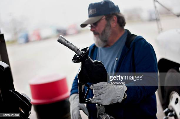 Customer Dave Graves returns the pump after filling his truck with fuel at a gas station in Princeton Illinois US on Tuesday Dec 18 2012 Retail...