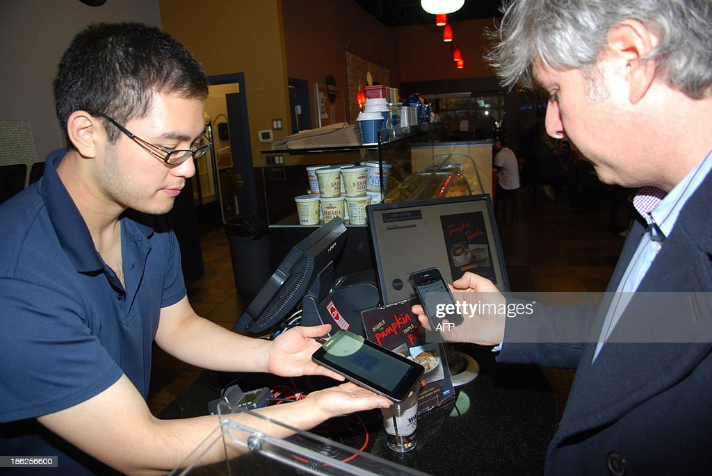 Customer David Lowy (R) uses his smart phone to pay .0101 bitcoins for a cup of dark coffee (worth about $2 US), from barista Chris Fujiki at the Waves coffee shop in downtown Vancouver on October 29, 2013. Three young entrepreneurs opened an automated teller Tuesday in this Western Canadian city, calling it the worlds first ATM able to exchange bitcoins for any official currency. The machine, delivered to Vancouver by Robocoin, an American manufacturer, stands against a wall of a popular coffee shop, resembles an ordinary cash ATM. However, instead of cash transactions it swaps Canadian dollars for bitcoins, the virtual currency of the Internet invented in 2008 by an anonymous computer scientist known only by the pseudonym Satoshi Nakamoto. AFP PHOTO / Deborah Jones