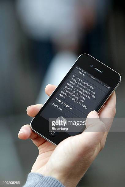A customer demonstrates the Siri function on an Apple Inc iPhone 4S smartphone outside the company's store at Covent Garden in London UK on Friday...