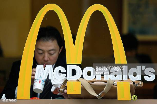 A customer dines behind a window at a McDonald's restaurant operated by McDonald's Holdings Co Japan Ltd in Tokyo Japan on Thursday Feb 5 2015...