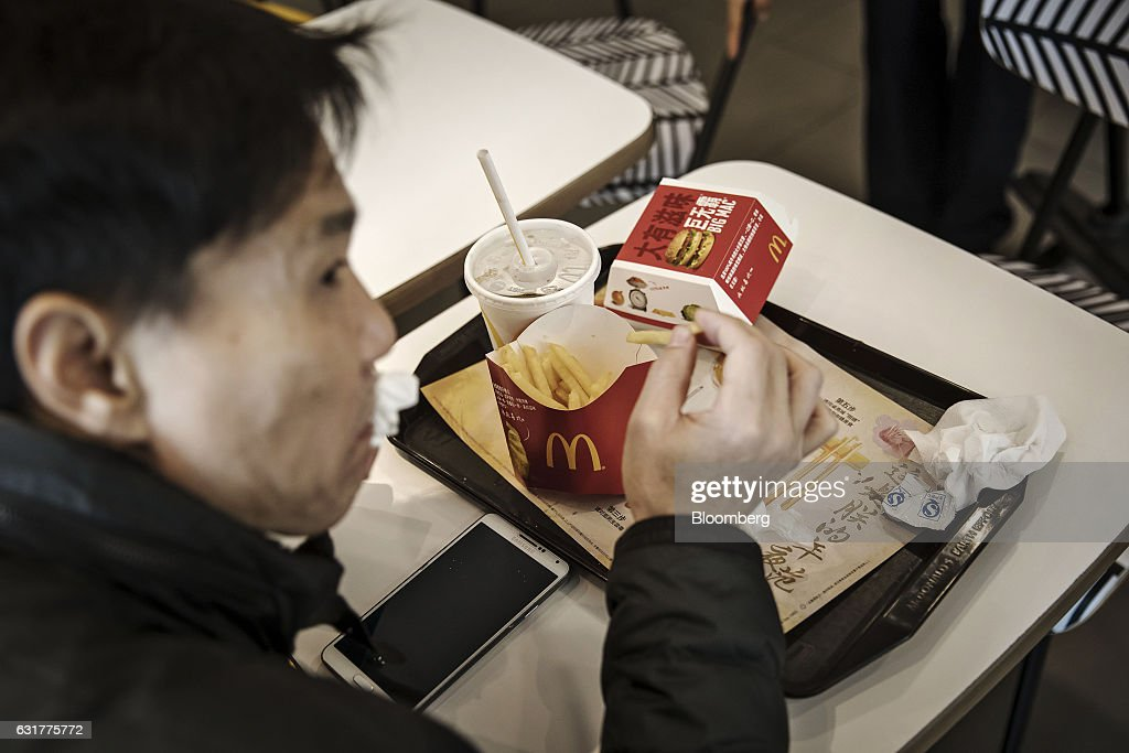 A customer dines inside a McDonald's Corp. restaurant in Shanghai, China, on Friday, Jan. 13, 2017. McDonald's agreed to sell a controlling stake in its China and Hong Kong operations to a group of investors for about $1.7 billion, a key component of the fast-food giants reorganization in a market where its striving to catch up with more nimble rivals. Photographer: Qilai Shen/Bloomberg via Getty Images