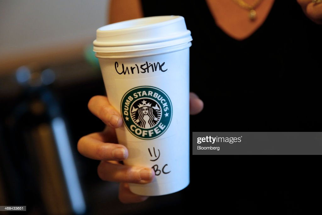 A customer displays a coffee cup for a photograph at the Dumb Starbucks Coffee store, a parody of the Starbucks Corp. coffee chain, in Los Angeles, California, U.S., on Monday, Feb. 10, 2014. Dumb Starbucks, which opened this past weekend, offered Dumb Vanilla Blonde Roast, Dumb Chai Tea Latte, and Dumb Caramel Macchiato, all available in sizes Dumb Venti, Dumb Grande, and Dumb Tall. Photographer: Patrick T. Fallon/Bloomberg via Getty Images