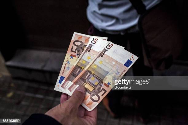 A customer displays three 50 euro banknotes withdrawn from a Banco de Sabadell SA bank branch in Barcelona Spain on Friday Oct 20 2017 In a video...