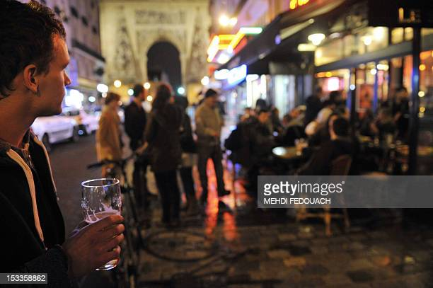 MULHOLLAND A customer drinks a beer outside the bar 'Le Sully' on October 4 2012 on Rue Du Faubourg SaintDenis in Paris The battle raging on Rue Du...