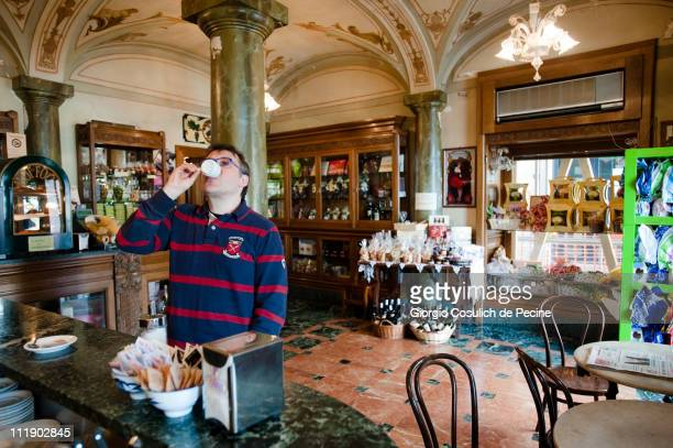 L'AQUILA ITALY APRIL 8 A customer drinks a coffe espresso inside the historic coffeshop and pastry 'Fratelli Nurzia' in a central street of L'Aquila...