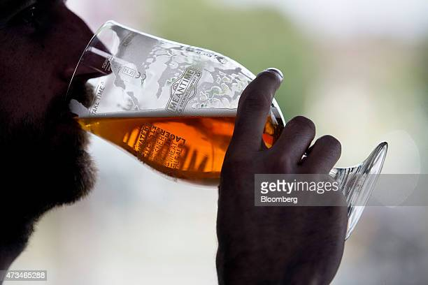 A customer drinks a glass of London Pale Ale in the tasting rooms at the Meantime Brewing Co brewery in London UK on Friday May 15 2015 SABMiller Plc...