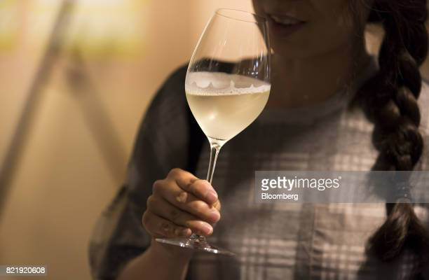 A customer drinks a glass of sparkling sake at the Japan Awasake Association booth during a Sake Marche event at the Isetan Shinjuku department store...