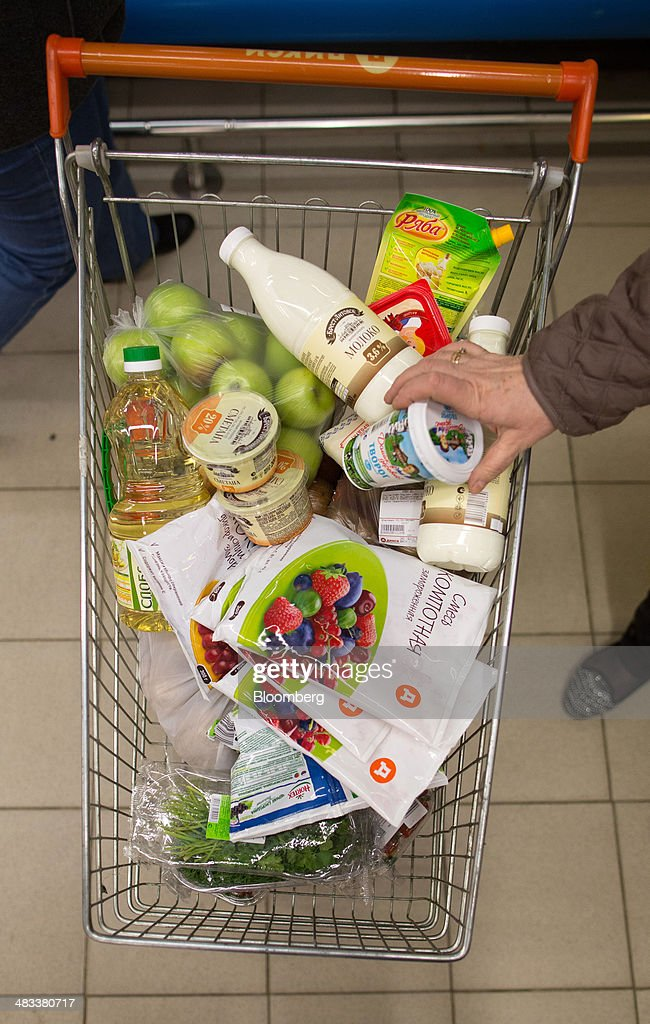 A customer drops products into a shopping cart inside a Dixy supermarket operated by OAO Dixy Group in Moscow, Russia, on Tuesday, April 8, 2014. Suppliers suffering from ruble depreciation this quarter are urging retailers to increase prices. Photographer: Andrey Rudakov/Bloomberg via Getty Images