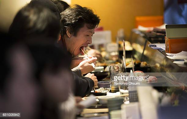 A customer eats a piece of sushi inside one of the company's Sushi Zanmai sushi restaurants after the year's first auction at Tsukiji Market on...