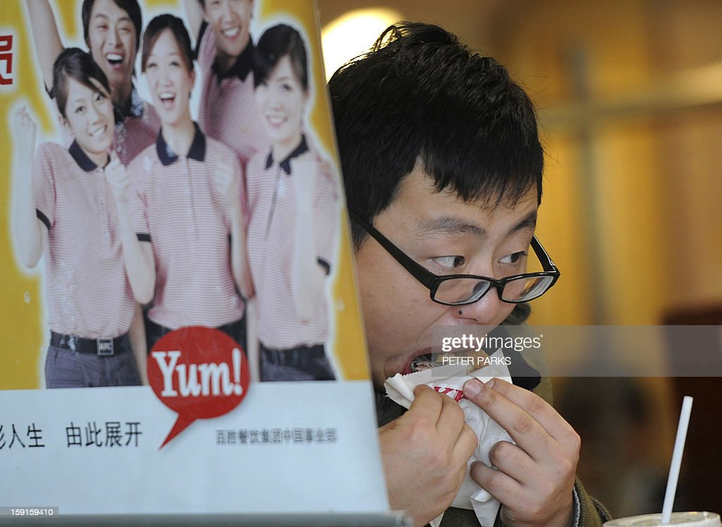 A customer eats Kentucky Fried Chicken (KFC) in an outlet in Shanghai on January 9, 2013. Chinese customers of KFC, the biggest fast food chain in the country, said they would still patronise it despite a government food safety investigation which has hit sales. US-based Yum! Brands Inc., whose portfolio includes KFC and Pizza Hut, said this week that sales in its key China market were forecast to fall more than expected in the fourth quarter in the wake of the probe into excess antibiotic levels in chickens. AFP PHOTO/Peter PARKS
