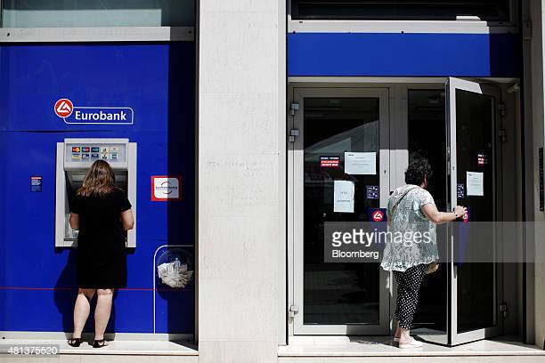 A customer enters a Eurobank Ergasias SA bank branch while another uses an automated teller machine in Athens Greece on Monday July 20 2015 German...