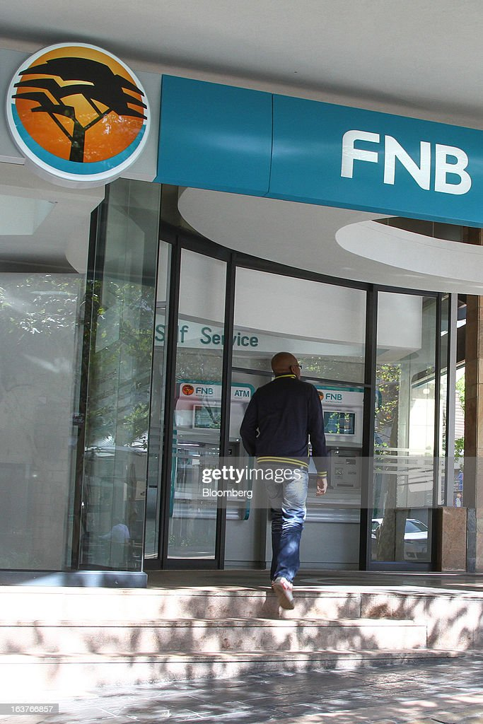 A customer enters a First National Bank (FNB) branch in Johannesburg, South Africa, on Friday, March 15, 2013. A recovery in mining and manufacturing is giving South Africa's rand and bonds a breather amid concern that growth is slowing while inflation accelerates. Photographer: Nadine Hutton/Bloomberg via Getty Images