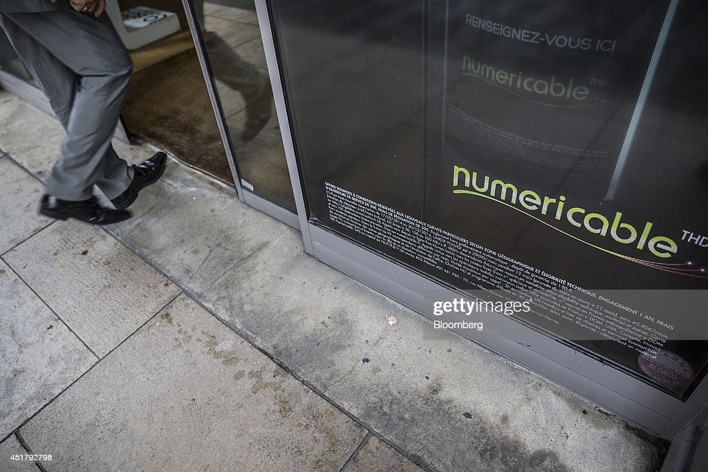 A customer enters a Numericable Group SA cable-television and internet store, operated by Altice SA, in Bordeaux, France, on Friday, July 4, 2014. Altice is raising its stake in Numericable after agreeing in April to merge the French cable provider with Vivendi SA's phone unit SFR, a transaction valued at more than 17 billion euros. Photographer: Balint Porneczi/Bloomberg via Getty Images