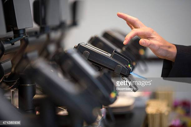 A customer enters their pin number as they make a chip and pin payment via a Verifone Systems Inc credit card payment device at a restaurant in...