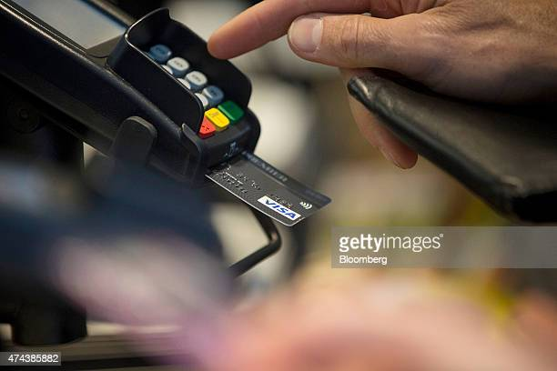 A customer enters their pin number while making a chip and pin payment using a Visa Inc payment card via a Verifone Systems Inc payment device at a...