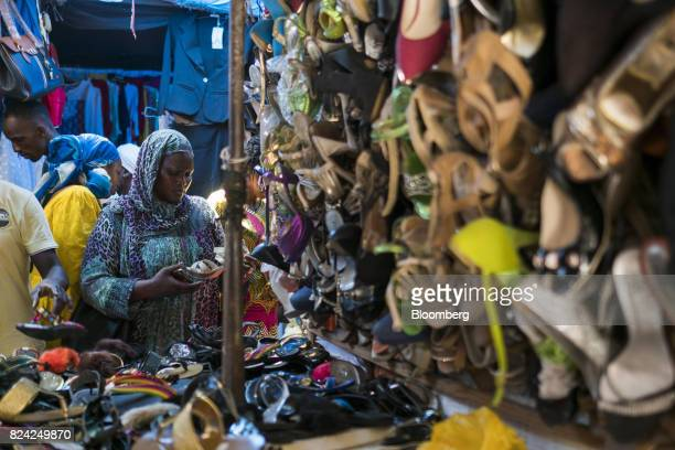 A customer examines a pair of shoes at the Sandaga market in the Plateau district of Dakar Senegal on Friday July 28 2017 Senegalese voters will...