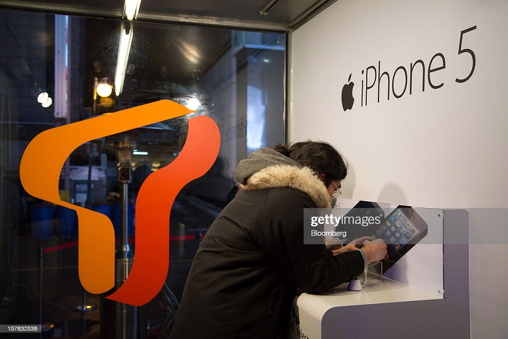 A customer examines an Apple Inc. iPhone 5 during a launch event organized by SK Telecom Co. in Seoul, South Korea, on Thursday, Dec. 6, 2012. The iPhone 5 went on sale in South Korea today. Photographer: SeongJoon Cho/Bloomberg via Getty Images