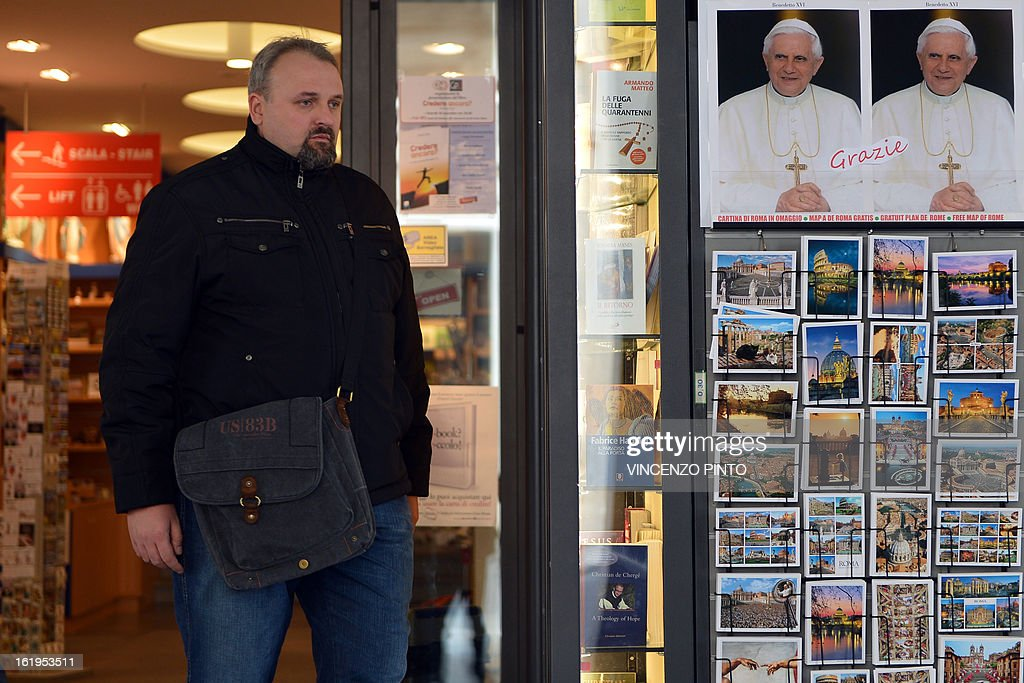 A customer exists a souvenirs shop where a note reading 'Thank you' had been sticked on portraits of Pope Benedict XV Inear the Vatican on Febraury 18, 2013 in Rome. Pope Benedict XVI began a week-long spiritual retreat out of the public eye on Monday ahead of his resignation on February 28, with the field of candidates to succeed him still wide open. AFP PHOTO / VINCENZO PINTO