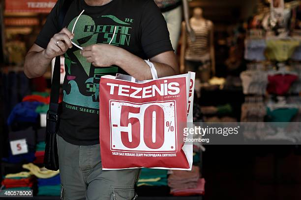 A customer exits a clothing store with a bag advertising 50% discounts during the summer sales in Athens Greece on Monday July 13 2015 Greece has...