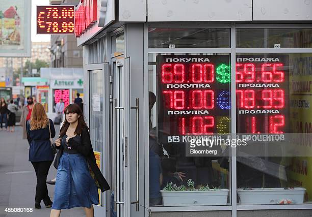 A customer exits a foreign currency exchange bureau advertising euro dollar and ruble rates in Moscow Russia on Sunday Aug 23 2015 The Russian ruble...