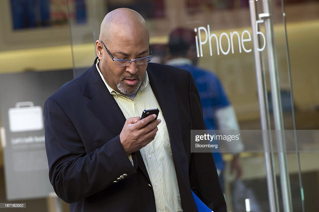 A customer exits an Apple Inc. store using an Apple Inc. iPhone in San Francisco, California, U.S., on Friday, April 19, 2013. Apple Inc. is expected to release earnings data on April 23. Photographer: David Paul Morris/Bloomberg via Getty Images