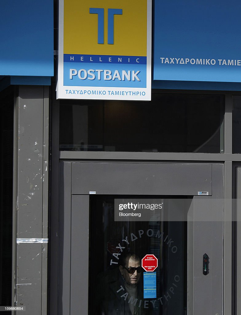 A customer exits an Hellenic Postbank SA bank branch in Athens, Greece, on Tuesday, Jan. 22, 2013. Euro-area finance ministers blessed the next disbursement of emergency aid for Greece, highlighting the goodwill that led to the unblocking of loans last month for Prime Minister Antonis Samaras's government. Photographer: Kostas Tsironis/Bloomberg via Getty Images