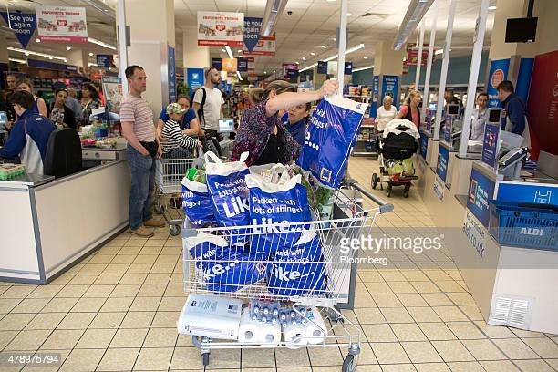 A customer fills her shopping cart with Aldi branded shopping bags after paying for her goods at the checkout counter inside an Aldi supermarket...