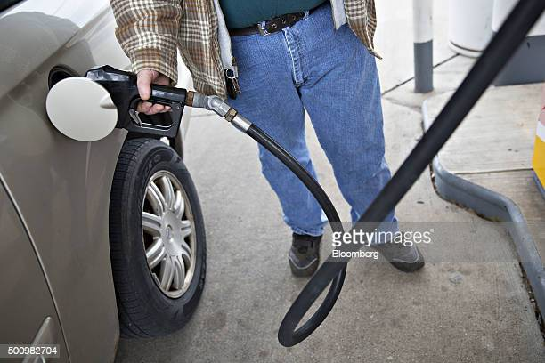 A customer fills his tank at a gas station in Creve Coeur Illinois US on Friday Dec 11 2015 The cost of a gallon of regular gasoline fell 67 percent...