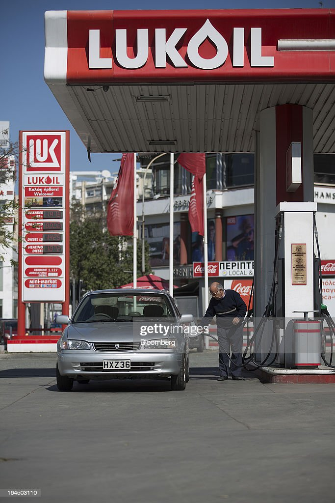 A customer fills his vehicle with fuel on the forecourt of an OAO Lukoil gas station in Nicosia, Cyprus, on Sunday, March 24, 2013. Cyprus's fate hangs in the balance as euro-area finance ministers meet today to decide whether the tiny Mediterranean island has done enough for a bailout that will avert its financial collapse. Photographer: Simon Dawson/Bloomberg via Getty Images