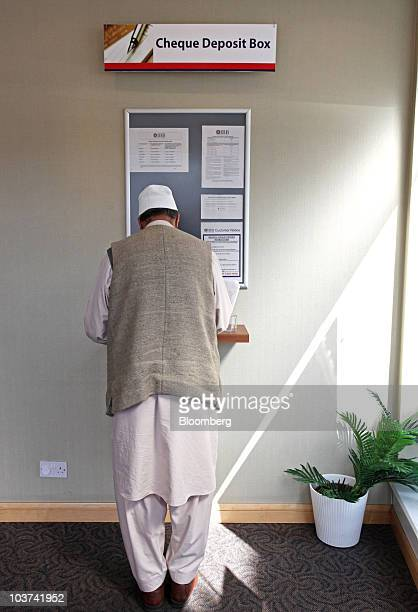 A customer fills out a cheque deposit form at a branch of the Islamic Bank of Britain Plc in Birmingham UK on Tuesday Aug 31 2010 Islamic Bank of...