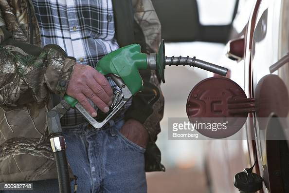 A customer fills their vehicle with fuel at a gas station in Chillicothe Illinois US on Friday Dec 11 2015 The cost of a gallon of regular gasoline...