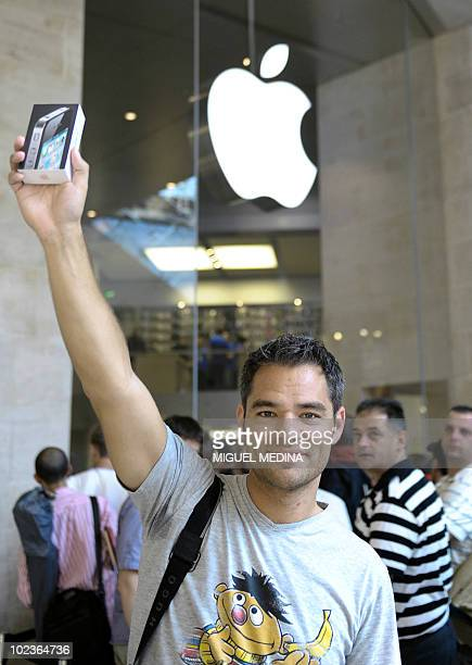 A customer from Netherlands Maurice who arrived at 4 am holds his iPhone 4 in front of a mobile phone store at the Carrousel du Louvre shopping mall...