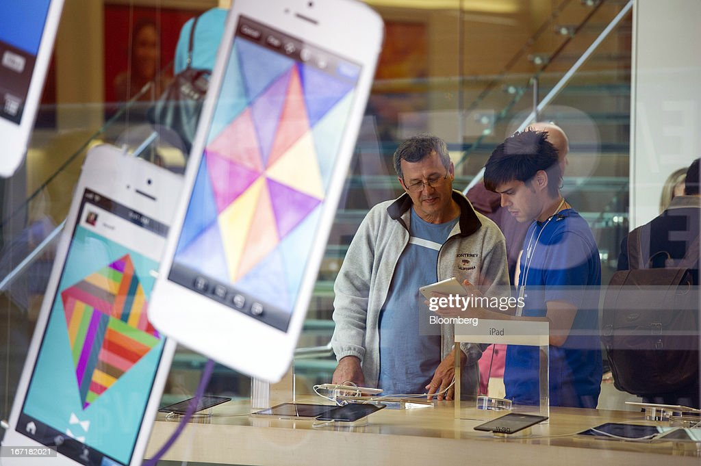 A customer gets help from an employee while looking at an iPad mini at an Apple Inc. store in San Francisco, California, U.S., on Friday, April 19, 2013. Apple Inc. is expected to release earnings data on April 23. Photographer: David Paul Morris/Bloomberg via Getty Images