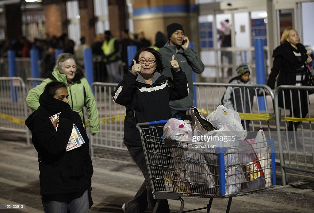 A customer gives the thumbs-up as she leaves with her purchased items outside Wal-Mart Thanksgiving day on November 28, 2013 in Troy, Michigan. Black Friday shopping began early this year with most major retailers opening their doors on Thanksgiving day as consumers took advantage of discounted prices to prepare for the holiday season.