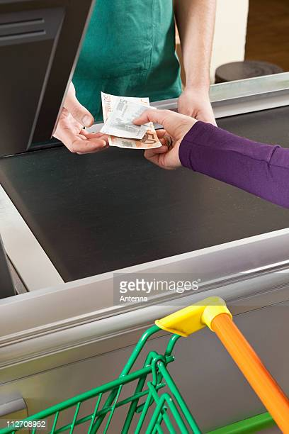 A customer handing a cashier cash at the supermarket