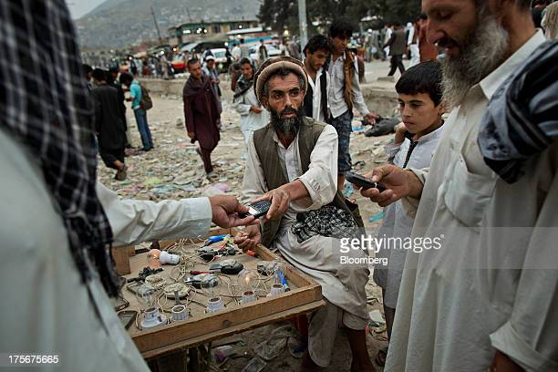 A customer hands a mobile phone to a man operating a mobile phone charging station in downtown Kabul Afghanistan on Saturday Aug 3 2013 A smooth US...