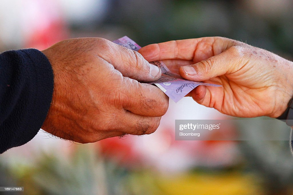 A customer hands an Australian five-dollar banknote to a vendor at the Frenchs Forest Organic Food Market in Sydney, Australia, on Sunday, May 19, 2013. The Reserve Bank of Australia cut its benchmark interest rate to a record low this month to boost businesses weakened by the currency's sustained strength, even as households reacted to earlier reductions. Photographer: Brendon Thorne/Bloomberg via Getty Images