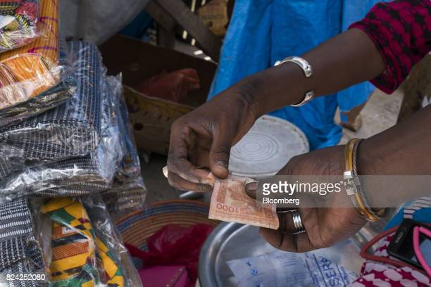A customer hands over a one thousand West African CFA franc currency banknote for goods at the Malian market in the Plateau district of Dakar Senegal...
