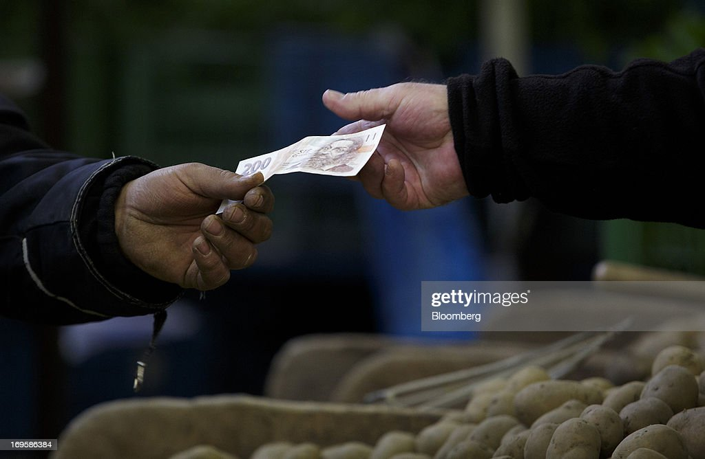 A customer hands over a two hundred denomination Czech koruna currency note at a vegetable stall in Holesovicka market hall in Prague, Czech Republic, on Monday, May 27, 2013. Czech policy makers are in uncharted territory as they debate whether the first koruna sales in a decade are needed to meet their inflation target as the economy has shrunk for five quarters, the longest contraction since at least 1996. Photographer: Martin Divisek/Bloomberg via Getty Images