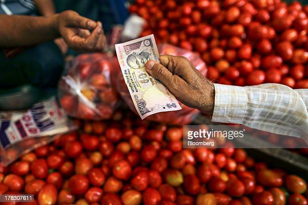 A customer hands over an Indian fifty rupee banknote to a vendor at the Laxmanrao Yadav vegetable market in Mumbai India on Wednesday Aug 28 2013...