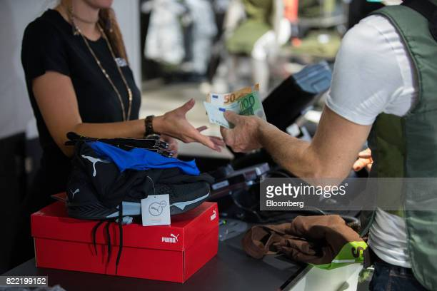 A customer hands over euro banknotes to a cashier inside a Puma SE sportswear clothing store in Berlin Germany on Tuesday July 25 2017 Puma increased...