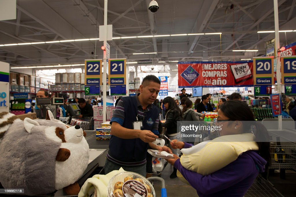 A customer holding a baby, right, pays for her merchandise inside a Sam's Club store in Mexico City, Mexico on Saturday, Nov. 17, 2012. El Buen Fin, Mexico's equivalent of Black Friday, when the year's biggest discounts are offered by participating stores, is held on the third weekend of November and will run through Nov. 19. Photographer: Susana Gonzalez/Bloomberg via Getty Images