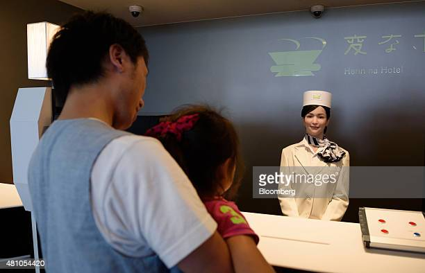 A customer holding a girl left looks at a Kokoro Company Ltd humanoid robot at the reception desk of Henn na Hotel operated by Huis Ten Bosch Co a...